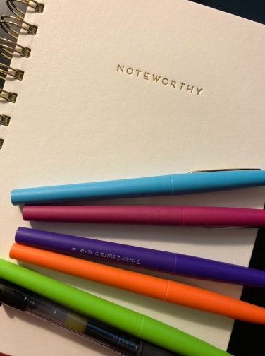 White Notebook with five different colored markers. Positive affirmation