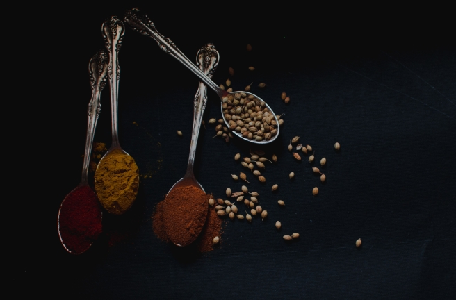 spoons filled with spices and seeds on black background